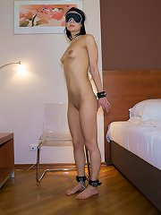 Blindfolded brunette standing all naked with cuffs on h..